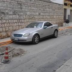 Lo scavo interrotto per colpa di un'auto in divieto di sosta