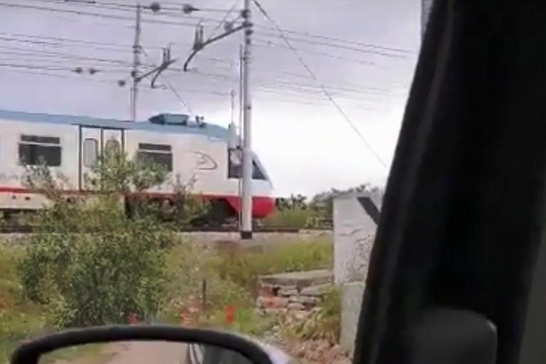 Treno in arrivo e passaggio a livello aperto